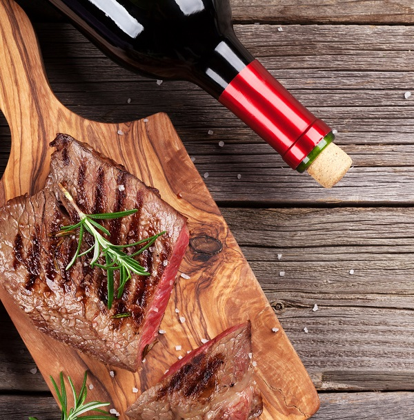 Grilled beef steak with rosemary, salt and pepper and red wine on wooden table. Top view with copy space